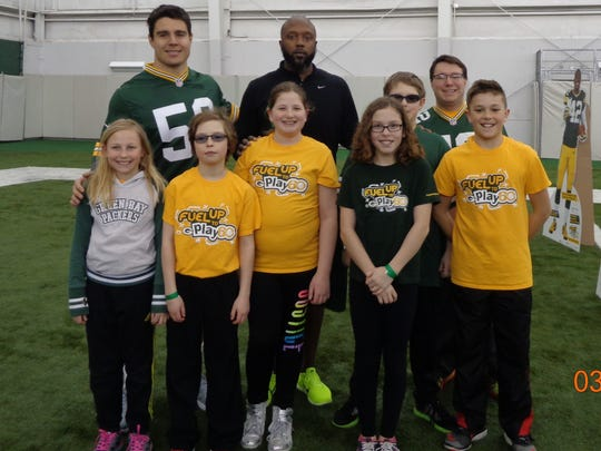 Makenna Kampmann, front from left, Aidan Maguire, Lauren Krembs, Ava Schoenrock and Thomas Passineau stop for a photo at Lambeau with Blake Martinez, back from left, Tony Fisher, Manning Ackley and teacher Kevin Podeweltz.