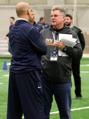 Coach James Franklin talks to an NFL scout at Penn State Pro Day. Nearly all of the 11 former Nittany Lions who worked out Thursday expect to be undrafted free agents.