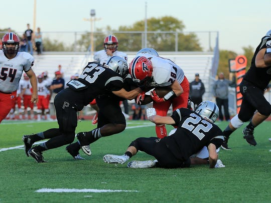 Nate Emminger (left) and Chase Timko (right) tackle Nate Binkiewicz.