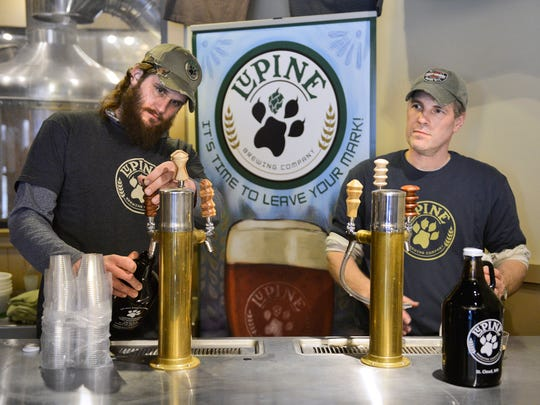 Lupine Brewing Co. Brewmaster Grant Aldrich, left, and President James Anderle fill growlers Thursday at the brewery in St. Cloud.