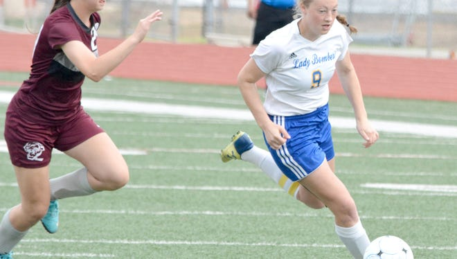 Mountain Home forward Emma Jones fights off a Benton defender during the first half on Saturday at Russellville.