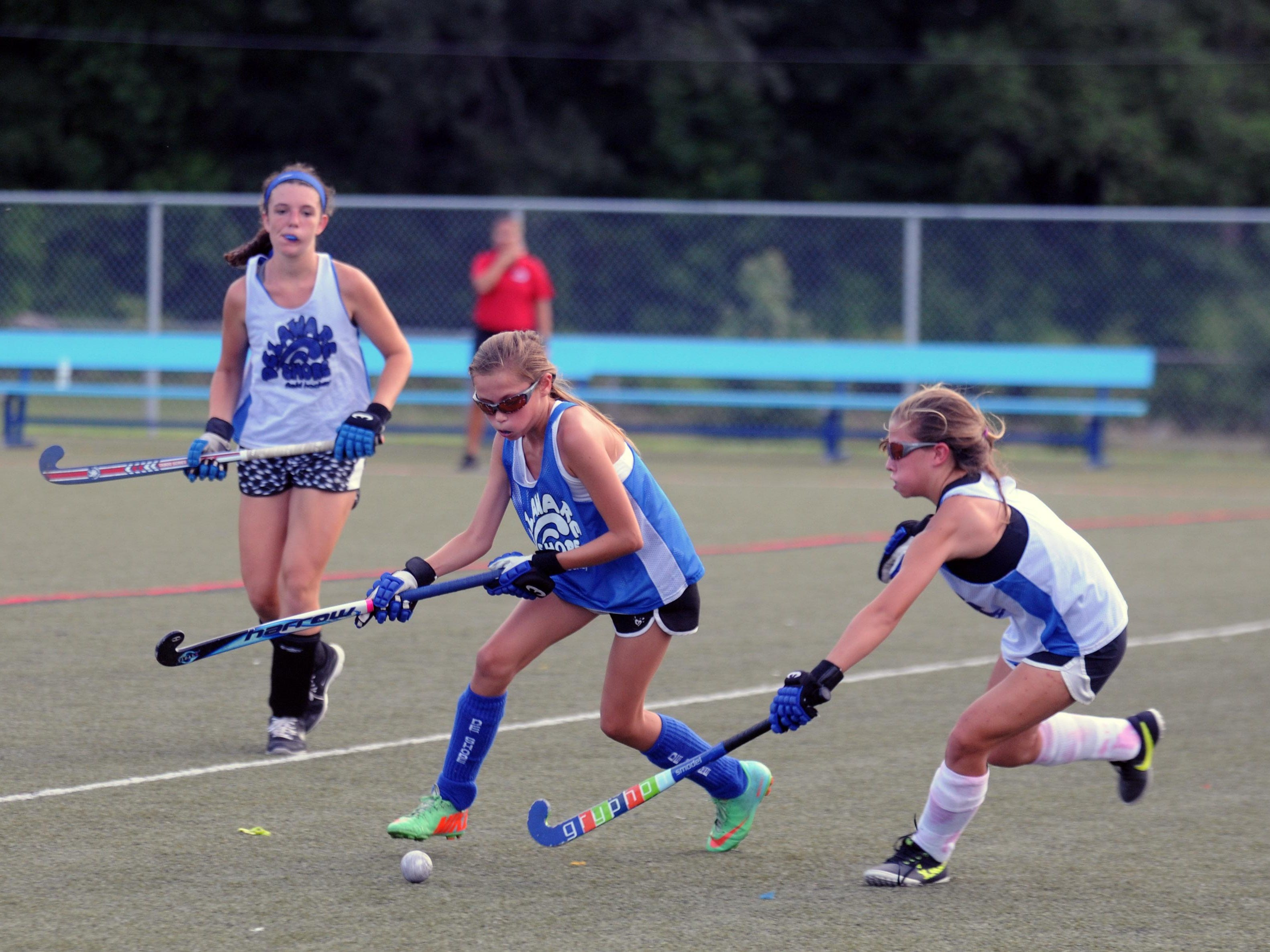 Players go for the ball and goalie during a summer league game for Delaware Shore Field Hockey at Cape Henlopen High School. Some of these players will be traveling with the U14 team to Disney World.