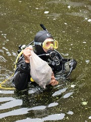 DNR diver Matt Schaeve surfaces in the Pigeon River with a bag of mussels.