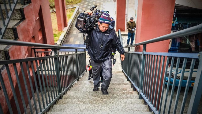 Alan Certeza carries camera equipment.