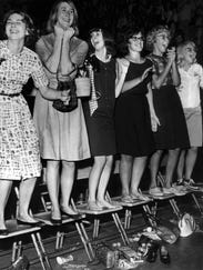 girls standing on chairs