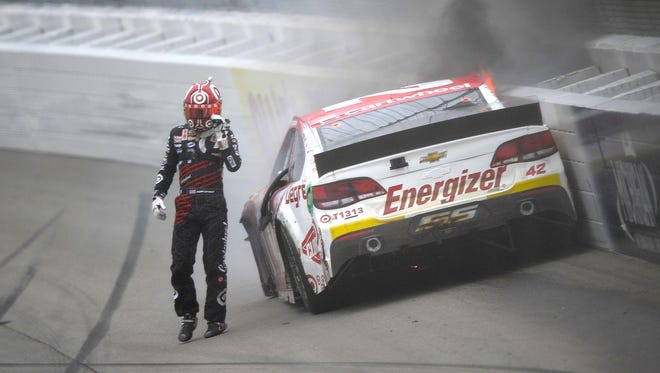 Kyle Larson steps away from his car after it caught fire when he slammed into the wall Sunday at Michigan International Speedway.