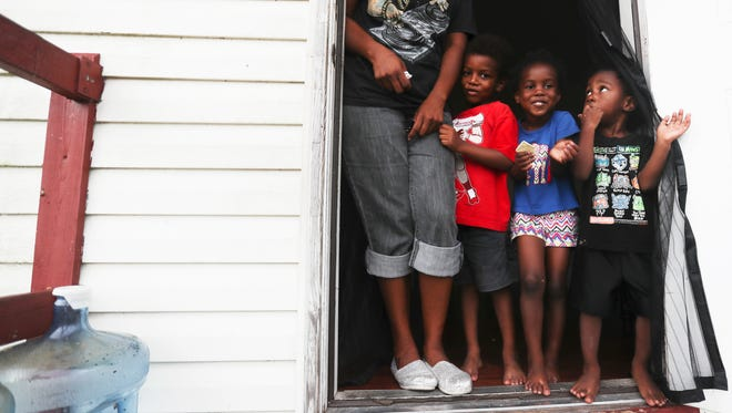 Sometime Charleston Park resident Christal Boldan, left, looks over her children, from left, Kani, 5, Kaniyah, 4, and Kai, 2 at her mother's home. The home is on well water. Bolden says her son, not pictured, gets rashes and she believes it is from the water. Her mother, Ella Christmas, has scars from rashes that developed from what she believes is the water as well. The family buys bottled water for drinking, but bathe and sometime brush their teeth with the well water. On the left is a jug that was once used as a water system for the home.