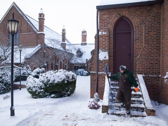 Chris Simmons, who owns Cutting Edge Lawn Care, walks down a set of shoveled stairs while doing snow removal at Trinity Episcopal Church in Staunton  on Tuesday, Feb. 17, 2015.