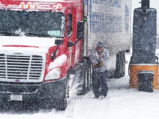 """Snow falls as long distance truck driver Florin Dumitru of Texas walks back to the cab of his truck.  He stopped long enough to fuel up at Pilot Travel Center near Greenville before continuing onward to Illinois on Saturday morning, Feb. 21, 2015.  """"It's so bad. .. It's so bad, I don't know if I can make it because of the weather,"""" says Dumitru. """"If you don't need to get out on the roads, stay home.  That's much better."""""""