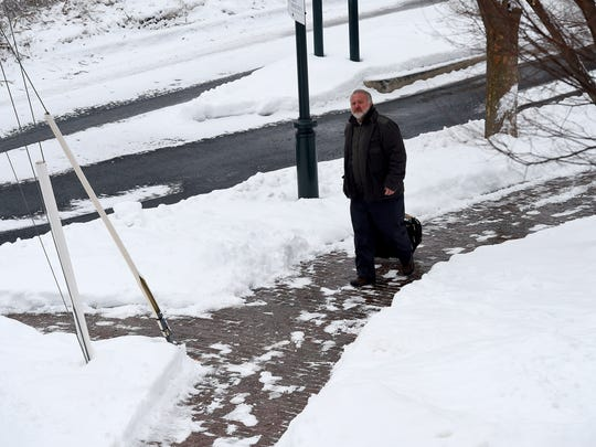 A pedestrian travels along one a cleared sidewalk at