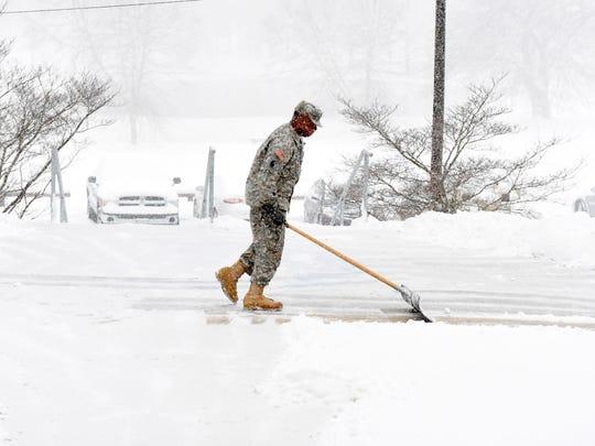 Staff Sgt. Deon Matthews scraps the snow off the walkway