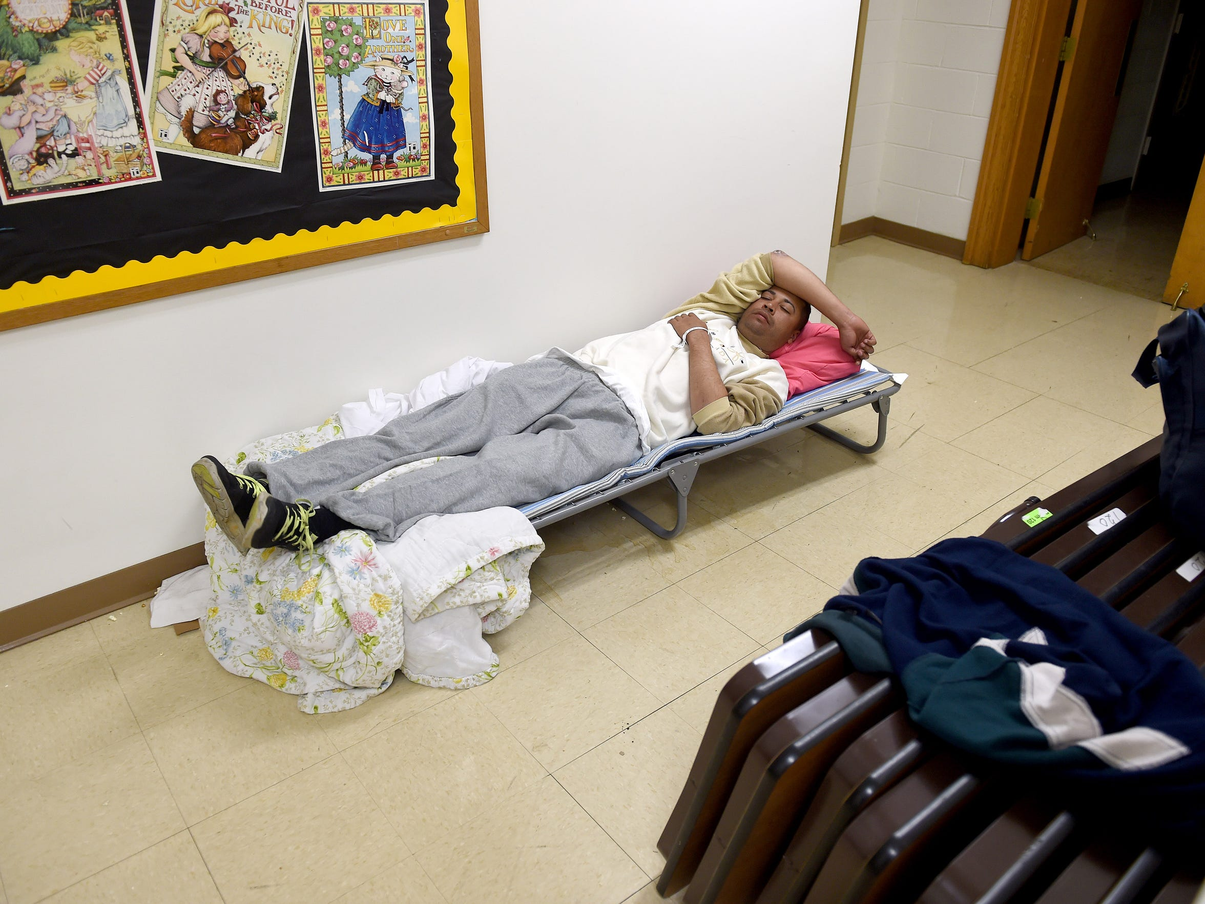 Carlos Basquez of New York rests on his assigned cot,