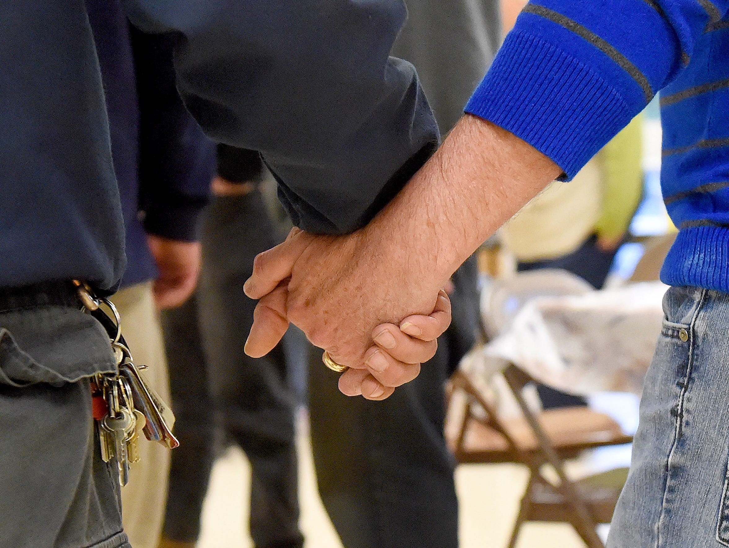 A volunteer clasps hands with a homeless person as