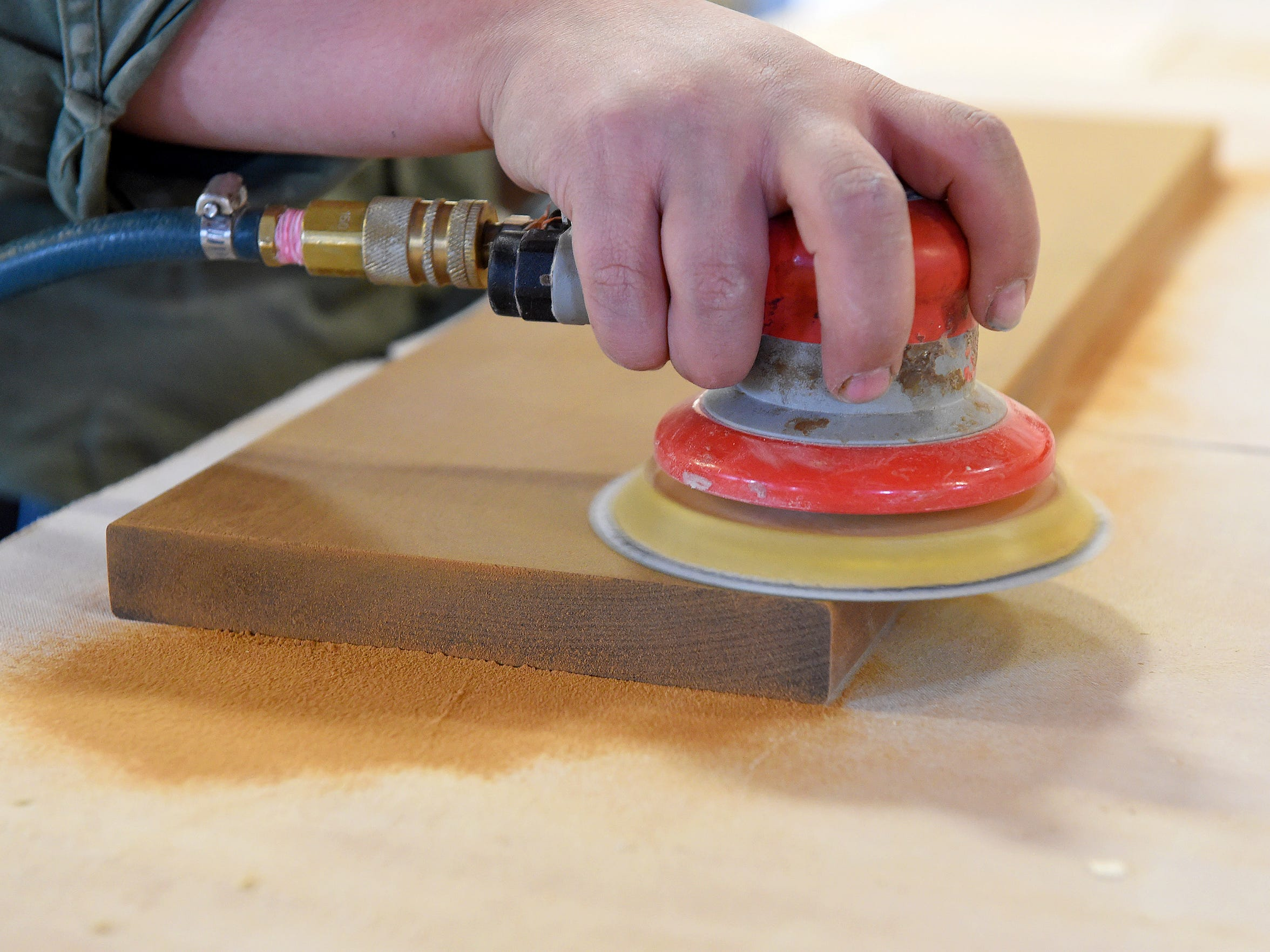 Morgan Bean uses a sander to smooth the sides of a