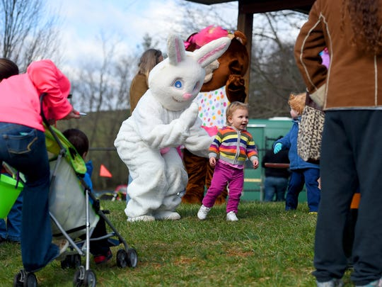 The Easter Bunny waves at Madeline Roberts, 2, of Staunton