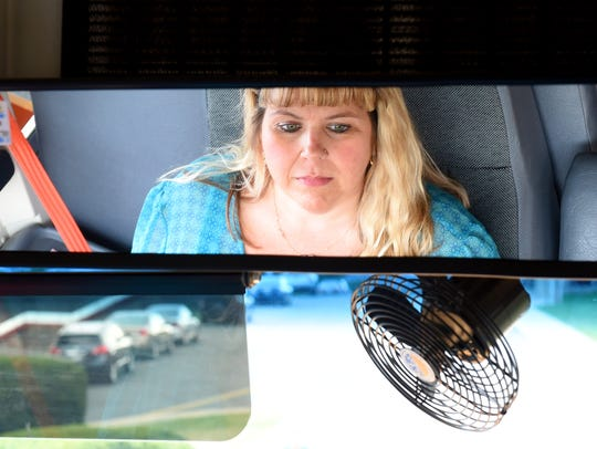 Bus driver Lisa Kisamore sits aboard her bus and waits