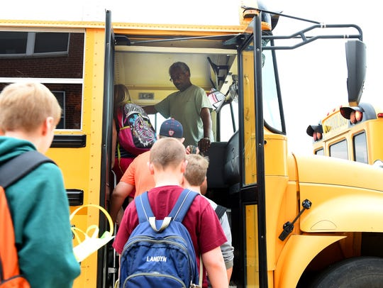 Bus driver Donald Strother watches as students board