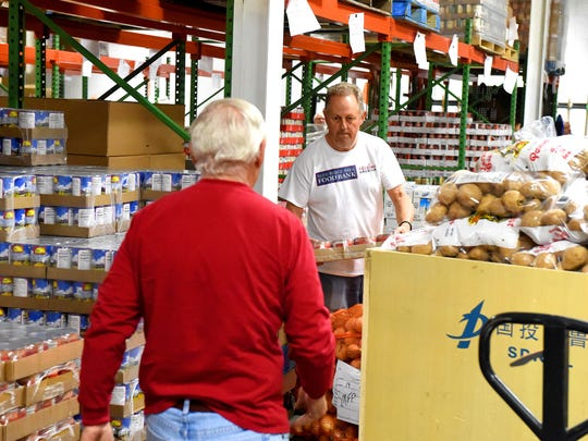 Volunteers Rick Kinkead (right) and Jay Young work together to pull items for a food order in the warehouse at the Blue Ridge Area Food Bank in Verona on Wednesday, April 8, 2015.