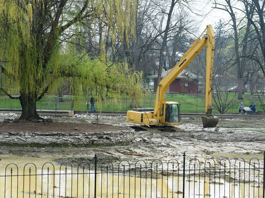 An excavator is used during during dredging operations taking place at the Gypsy Hill Park's duck pond on Wednesday, April 8, 2015.