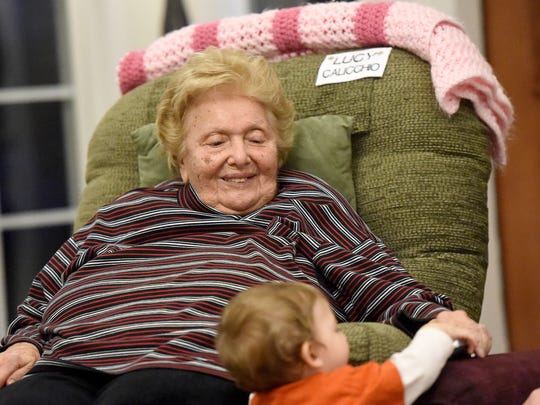 Lucy Callecio watches young Melvin Bender II and smiles at the young child's curiosity. She spends time socializing with others gathered in the living room at the Blue Ridge Christian Home in Raphine Wednesday, April 15, 2015.