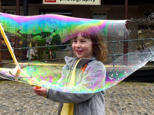Emma Rose Shirey, 5, of New Hope forms very large bubbles, which begins to pop, while at Bridge Day, honoring Sears Hill Bridge, at the train station in Staunton on Saturday, April 25, 2015.