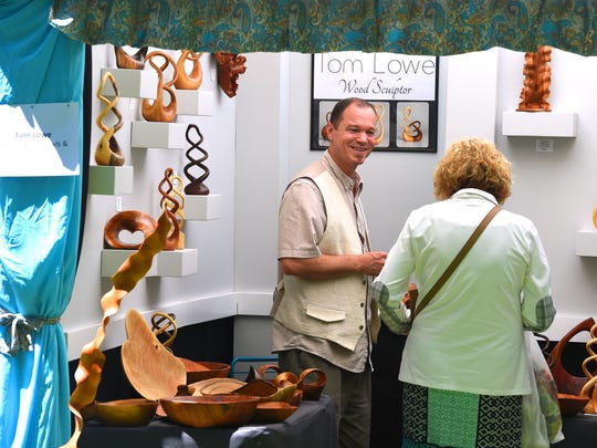 Wood sculptor Tom Lowe smiles as he discusses his work and style with a person visiting his vendor booth at the 49th annual Art in the Park at Gypsy Hill Park.