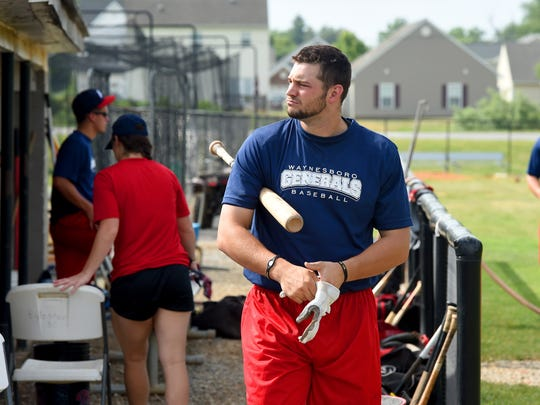Bat under one arm, Waynesboro Generals' first baseman Shane Dressler slips on his gloves as he prepares for batting practice on Thursday, June 18, 2015. Batters like Dressler find the new low seam baseballs a welcome change