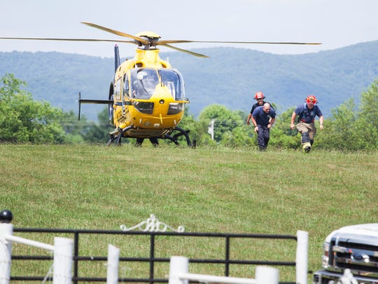 Emergency responders walk away from a medevac helicopter after loading a patient into the aircraft following a fire in Dooms on Monday, June 22, 2015.
