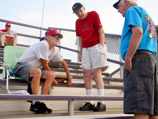 Quinlyn Dofflemyer sets up a seat cushion  for Thomas Lowery, center, who will sit next to him. Both plan to watch the Waynesboro Generals' home game against the Staunton Braves at Katie Collins Field on Wednesday, July 15, 2015. Whereas Dofflemyer has been a fan of the Generals for the past 7 or 8 years, Lowery marks decades as a fan.