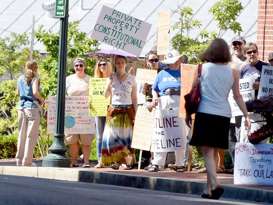 Demonstrators rally together to protest Dominion's