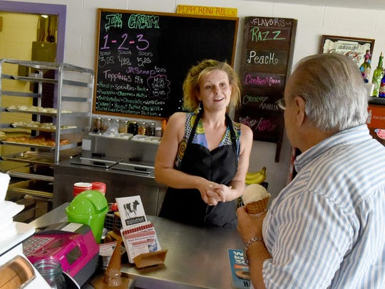 Business owner Becky Kincaid socializes with a costumer