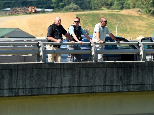 Law enforcement officers keep watch from the Va. 612 bridge over Interstate 81 at Verona on Wednesday, August 26, 2015. Law enforcement agencies were conducting a manhunt for shooting suspect Vester Flanagan at the time.