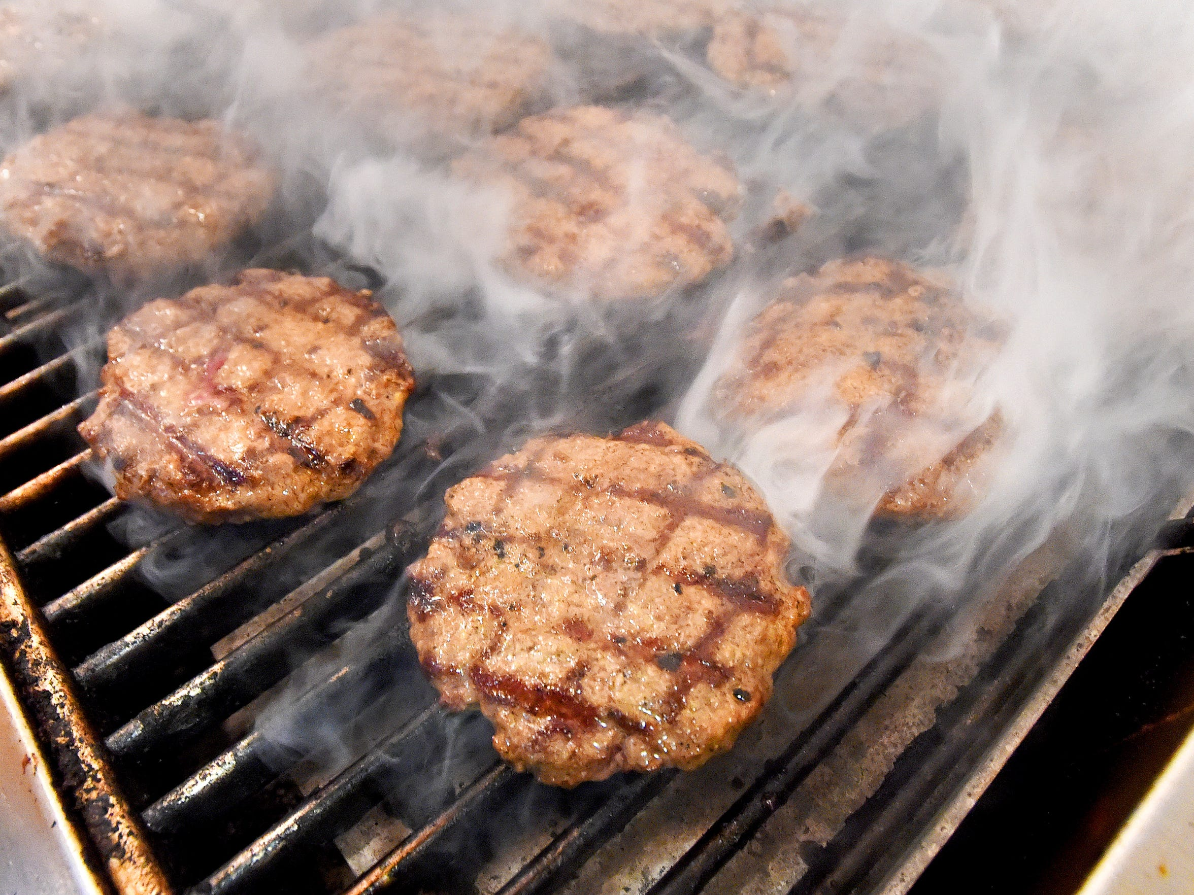 Burgers cook in the grill in the kitchen at DAP'S Ice