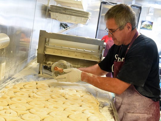 Ernie Schrock cuts donut shapes into the dough as he