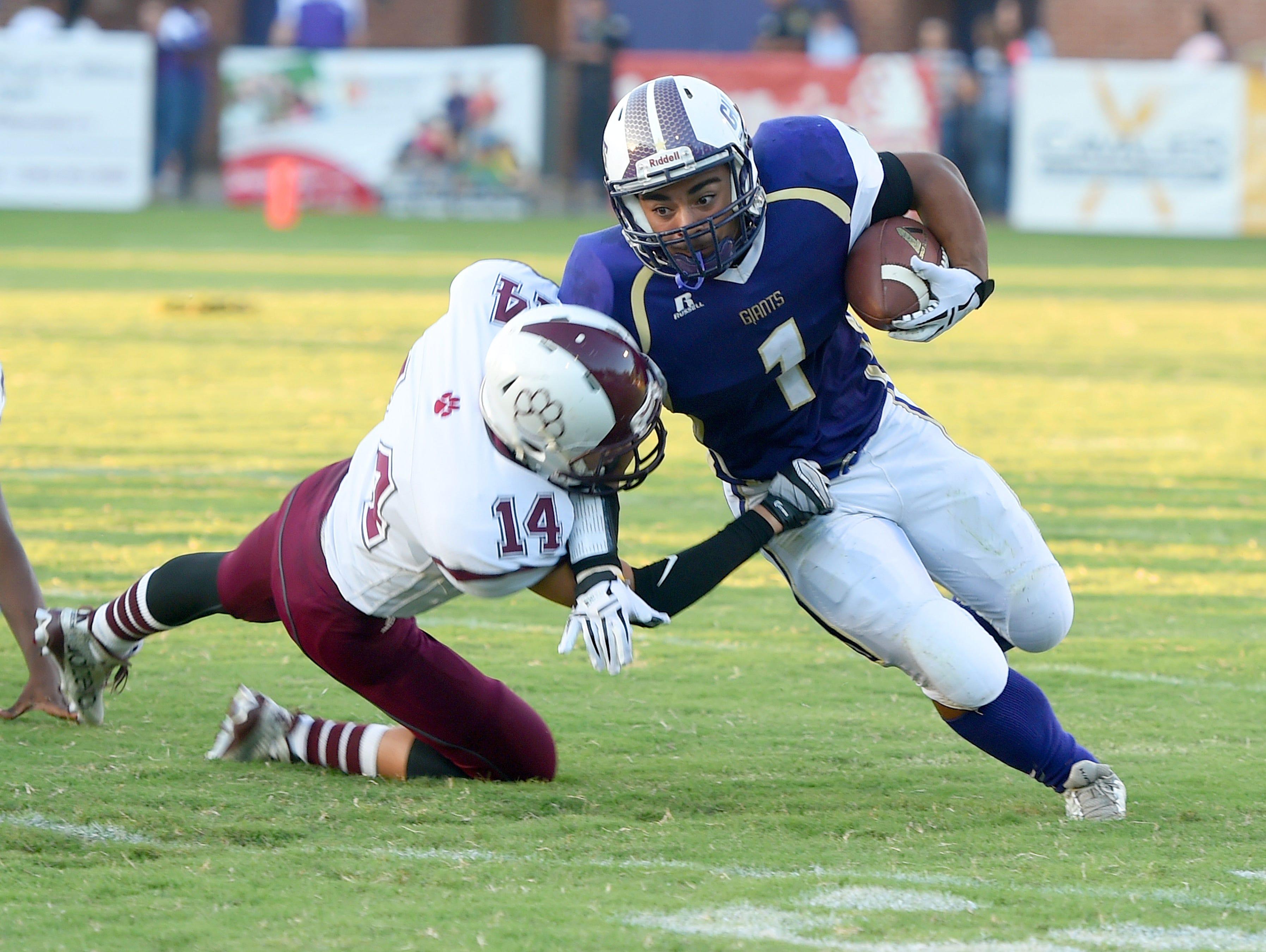 Waynesboro's Marendon Armon Jones tries to slip around Stuarts Draft's Trevor Craig who reaches for a tackle during a football game played in Waynesboro on Friday, Sept. 11, 2015.
