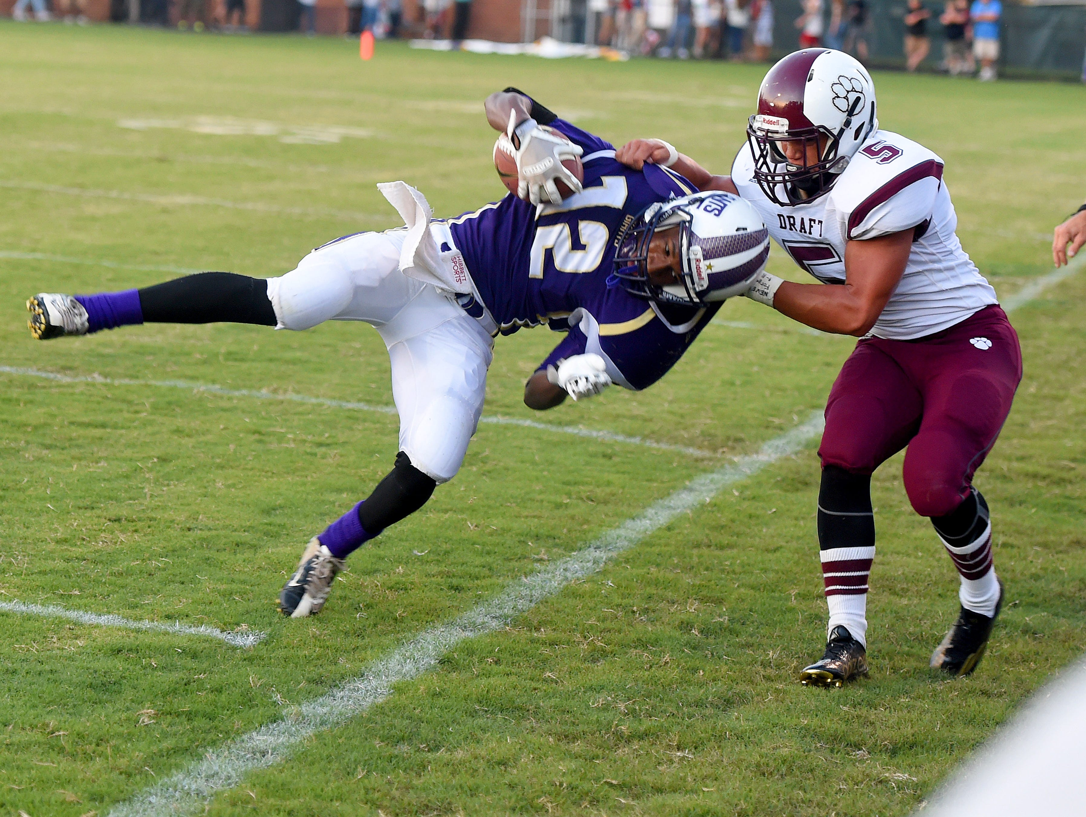 Waynesboro's Jequintus Chambers holds onto the ball as Stuarts Draft's Brandon Terrell yanks him off his feet during a football game played in Waynesboro on Friday, Sept. 11, 2015.