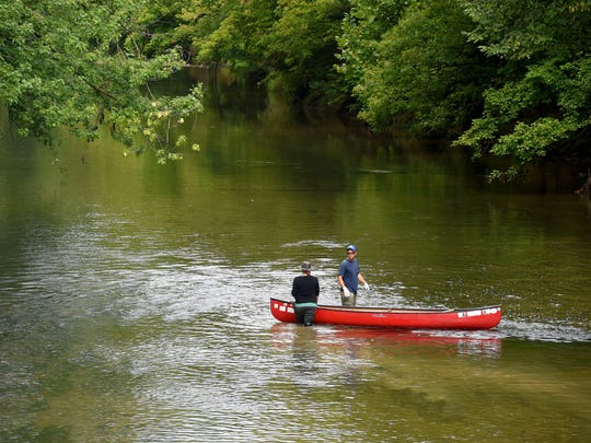 Sarah and Chad Rhinehart of Verona walk slowly downriver in the Middle River, pulling their boat with them even as they look for trash. The couple participates in Friends of the Middle River's annual Middle River Cleanup Day on Saturday, Sept. 12, 2015.