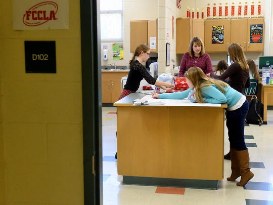 FCCLA advisor Jessica McCray (center) works with FCCLA members 8th-graders Abby Soyars and Kirsten Hildebrand as well as 6th-grader Reagan Mundie to make decorations, for an upcoming Breakfast with Santa event, after school at Wilson Middle School on Monday, Nov. 23, 2015. Scheduled for December 12, the event will be held by the schoolÕs FCCLA at Bridge Church in Fishersville and serves as a benefit for Brayden Kier and Aubrey Gutshall-McCray.