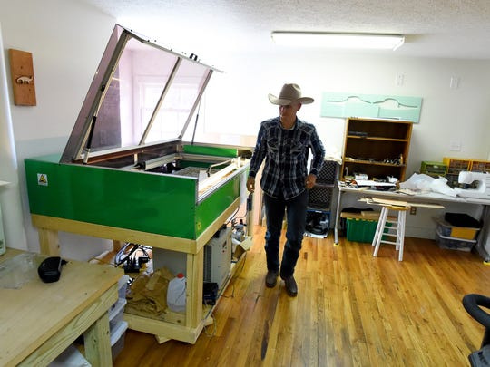 Local inventor Josh Lotts walks past the Lasersaur at Staunton Makerspace he used in helping to fabricate the 'ZRO trigger' he invented to be used with certain RC vehicle controllers on Wednesday, Dec. 9, 2015.
