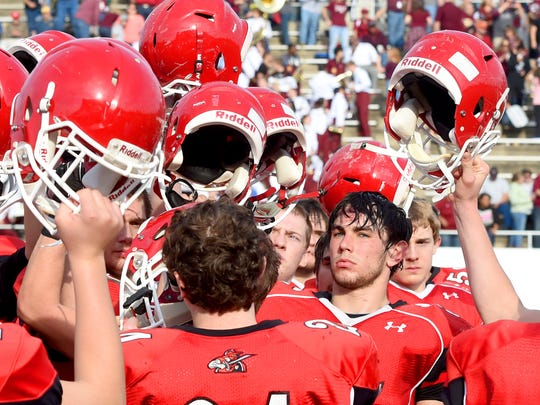 Riverheads' Hunter Allen stands stoic with his teammates as they lift their helmets after their Group 1A football championship game in Salem on Saturday, Dec. 12, 2015. Riverheads lost to Galax 7-6.