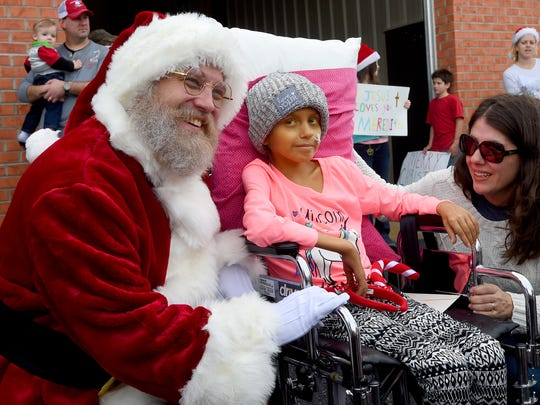 Ten-year-old Meredith Furr  smiles a tiny smile as she sits in her wheelchair between Santa Claus and her mother, Misti Furr. Meredith stopped briefly at the Stuarts Draft Rescue Squad building to visit with those gathered in support of her on Thursday, Dec, 24, 2015. After spending many months in the hospital, the 10-year-old asked her doctors to let her come home for the holidays and the doctors are granting her Christmas wish. Supporters gathering along her route to welcome her home.