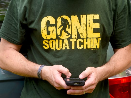 "Bigfoot researcher Mark Oswell wears a ""Gone Squatchin'"" t-shirt as he checks his phone. The East Coast Bigfoot Research Organization searched the George Washington National Forest near Elkhorn Lake for evidence of Sasquatch during a weekend investigation on June 20, 2015."