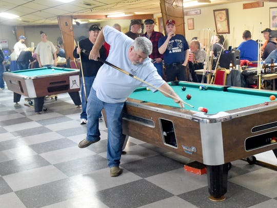Sherwood Cottrell of Fredericksburg goes up on one foot to make the shot. He warms up during a friendly game of 10-ball before the start of doubles competition during a regional pool tournament held at the Loyal Order of Moose Staunton Lodge 1635 on Saturday, Jan. 9, 2016.