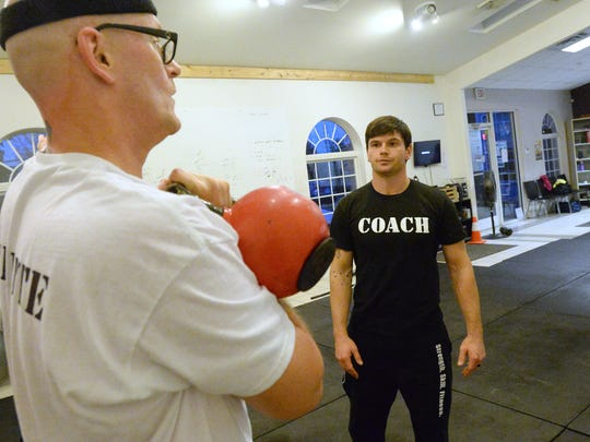 Co-owner of CrossFit Staunton, Phil Lennon keeps a close eye on the technique of Tony Robinson who uses a kettlebell. on Friday, Nov. 7, 2014, when the studio was located on Greenhills Drive just outside of Staunton.