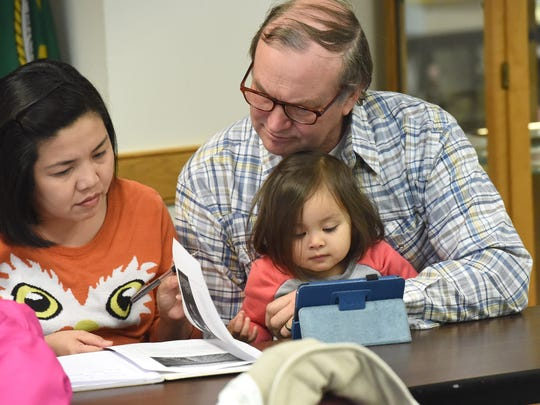 Leony Spieker(left) and husband Jeffrey Spieker of Sherando look through a handout on reclamation of drastically disturbed lands as their 3-year-old daughter watches a cartoon on their tablet. They attend pipeline landowner seminar held at the Augusta County Government Center on Thursday, Jan. 21, 2016.