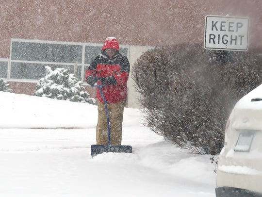 A man clears snow near the emergency room entrance