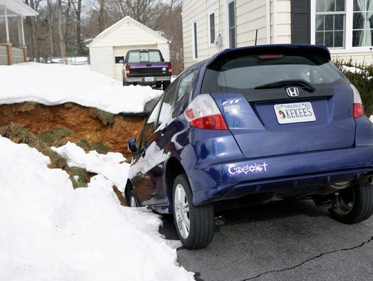 A Honda Fit is balanced on the edge of a sinkhole that