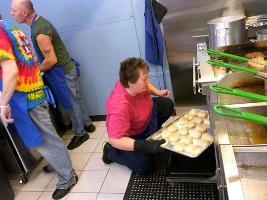 Co-owner Tammy Johnson rotates a tray of biscuits cooking