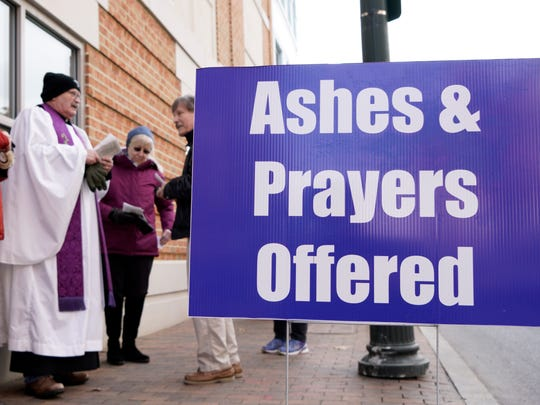 A sign lets those passing by know that a group, from several different churches, gathered in front of Staunton's City Hall are offering to apply ashes to the foreheads of  individuals wishing as well as pray with them on Ash Wednesday in downtown Staunton on Feb. 10, 2016.