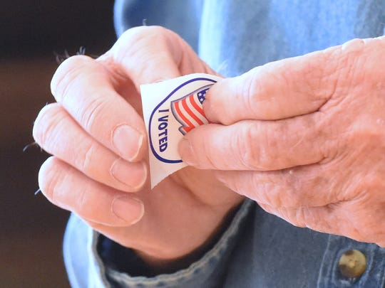"A resident of Augusta County, Meredith Moran of Staunton peels his ""I Voted"" sticker off its backing to stick it on his shirt after voting at the Middlebrook precinct during the primary elections on Tuesday, March 1, 2016."